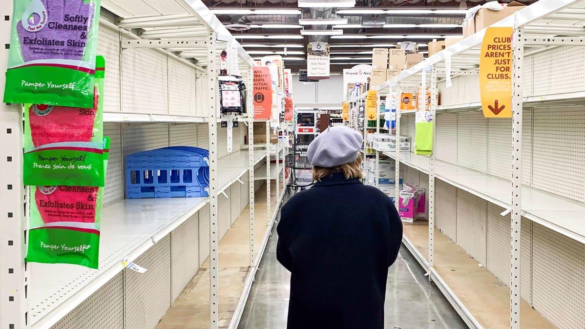 Naine seisoo tyhjien hyllyjen keskellä kaupassa Kaliforniassa.
