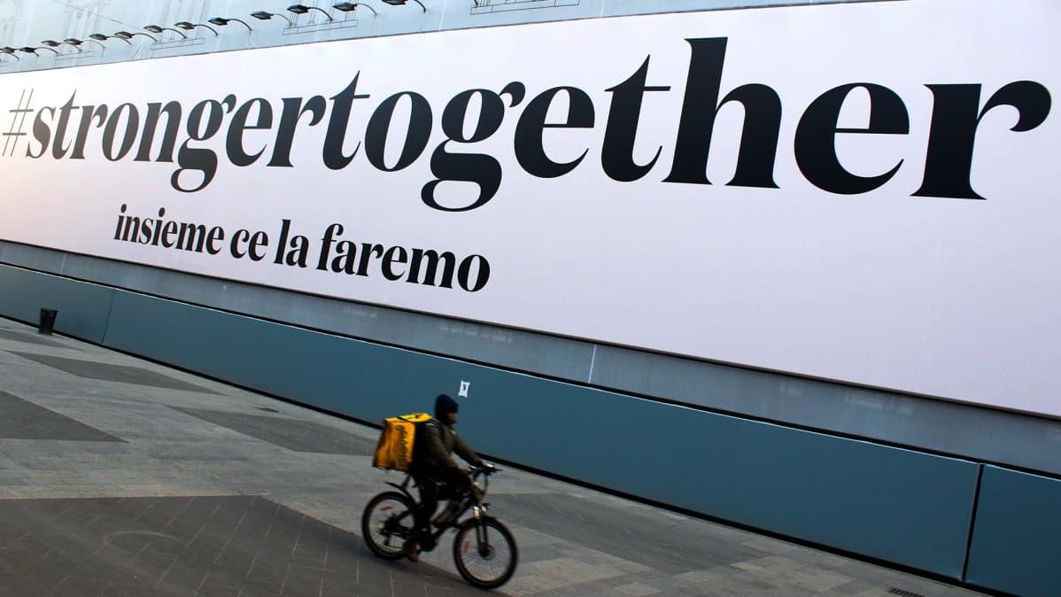 Kyltti Milanossa jossa lukee hastag strongertogether ja sen alla together we'll make it.