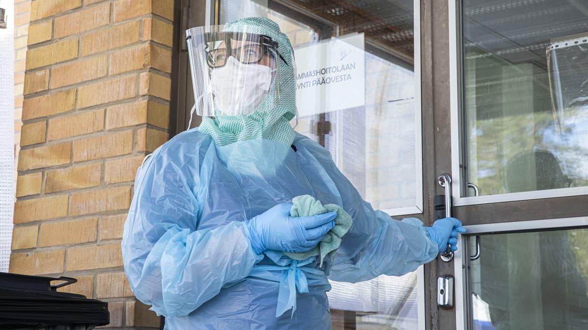 Hoitaja Varkauden sairaalan koronaosaston ovella suojavarusteissa.
