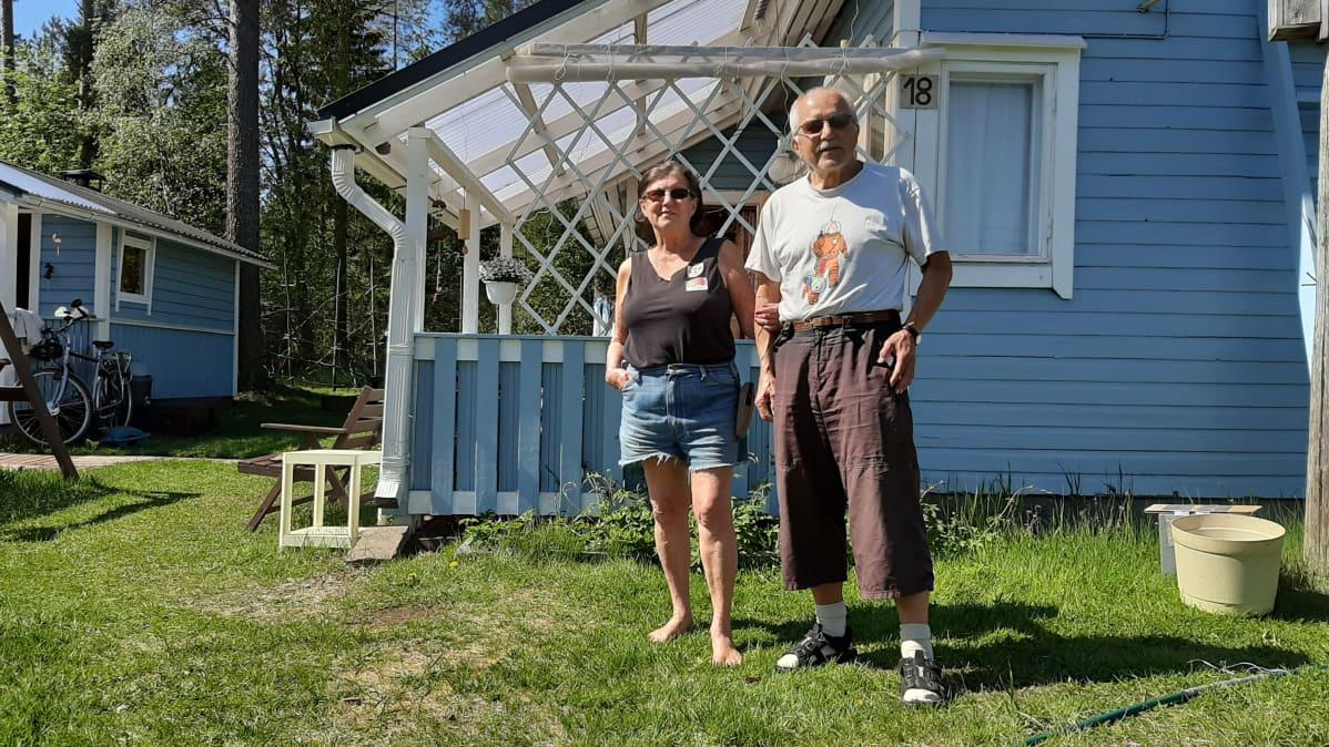 Nainen ja mies seisovat siirtolapuutarhan edustalla.