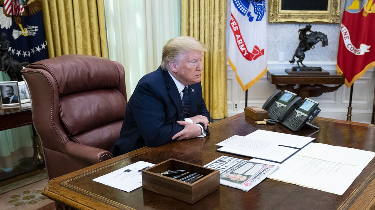 Dinald Trump istuu työpöydän ääressä.