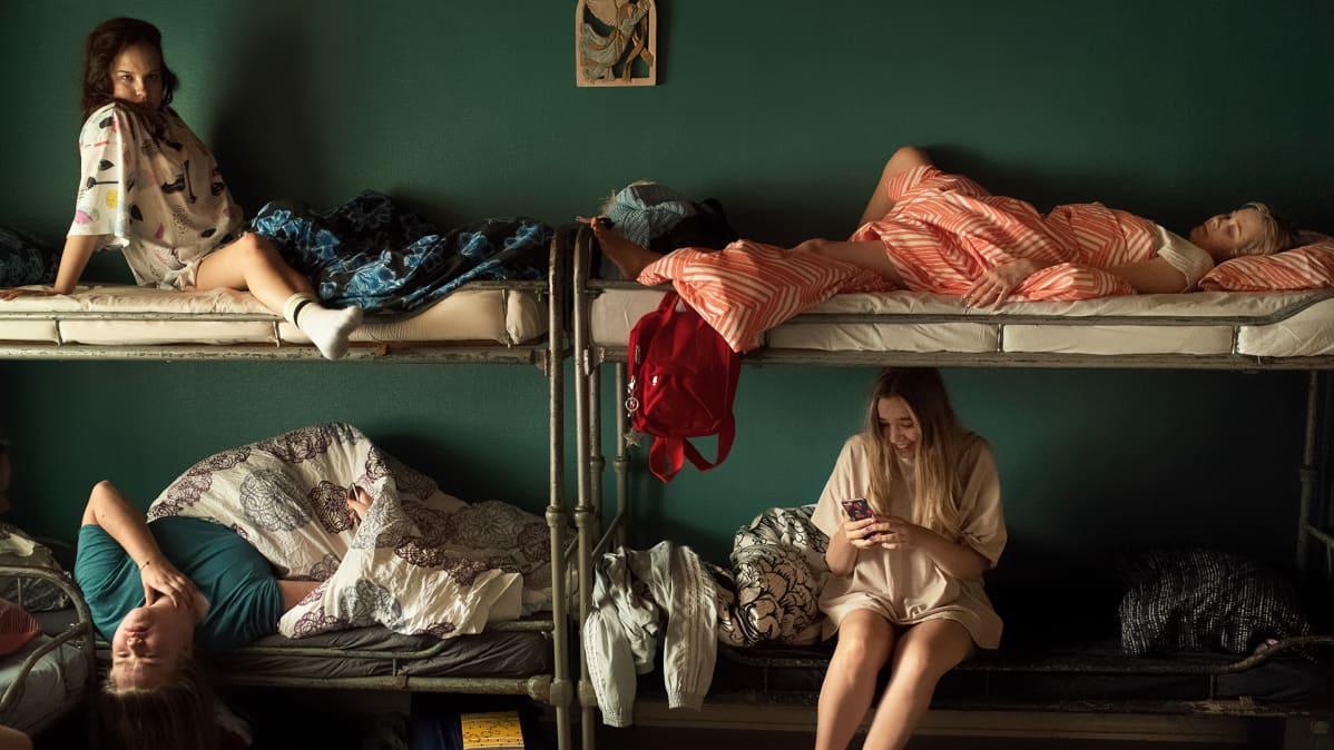 Kuvassa Eden- elokuvan hahmoja kerrossängyilla istumassa ja makaamassa erilaisissa asennoissa. Heidän takanaan on vihreä seinä.