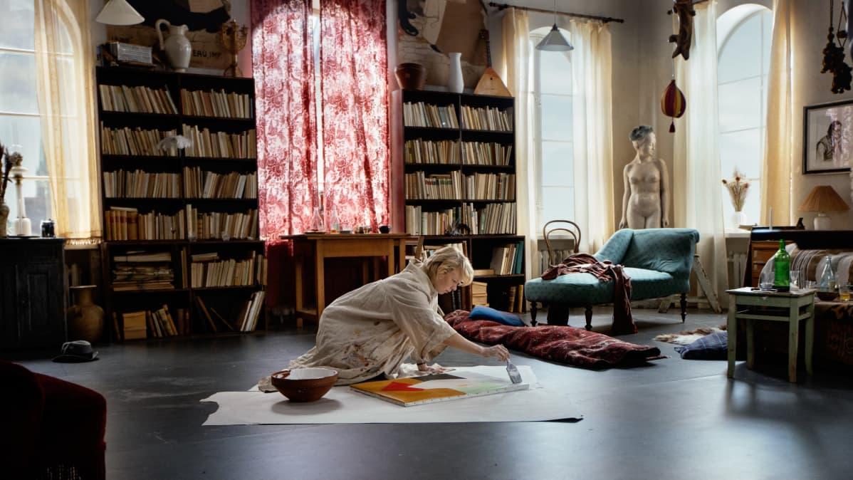 Kuvassa Alma Pöysti, joka maalaa lattialla.