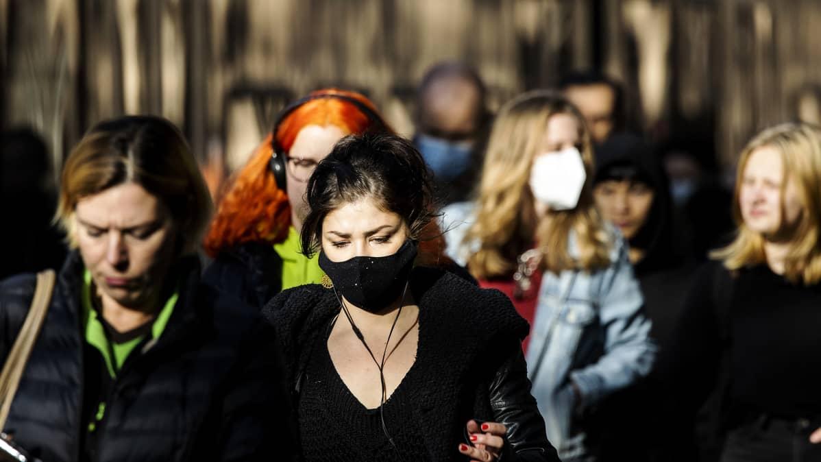 Maski kasvoillaan kulkevia ihmisiä Helsingin keskustassa.