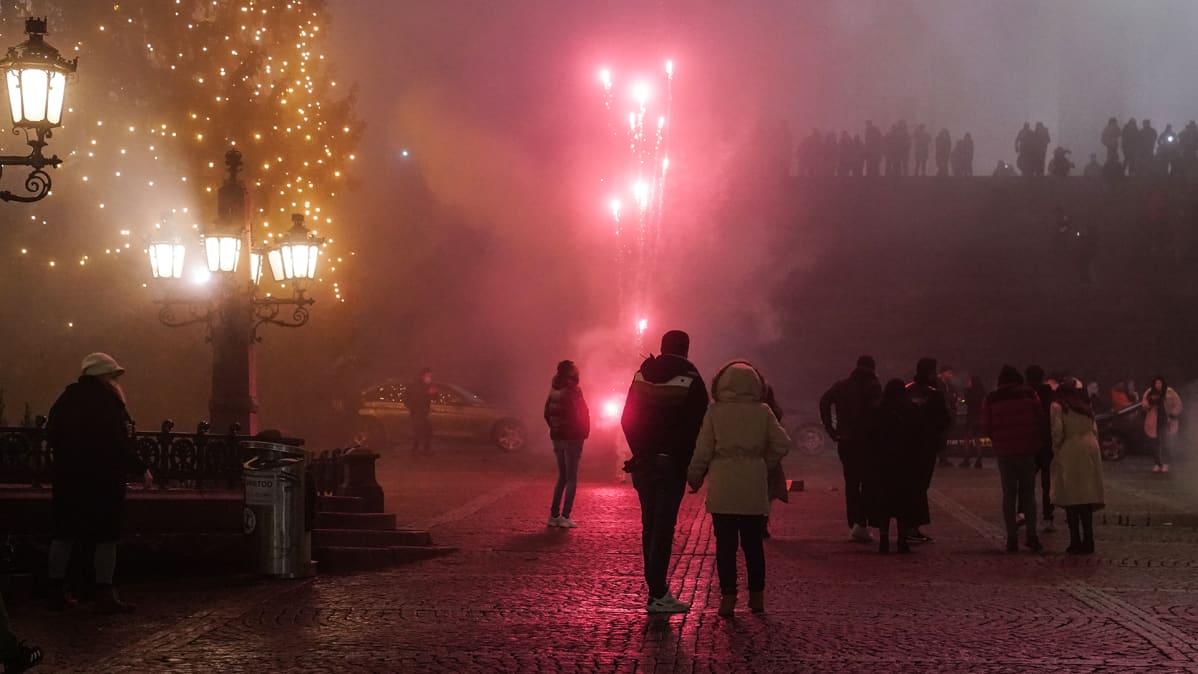 Ihmisiä Senaatintorilla uutena vuonna puolilta öin.
