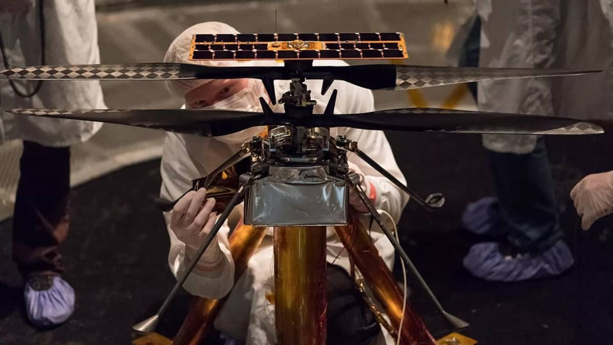Suojavaatteisiin pukeutunut tutkija säätää pientä helikopteria.