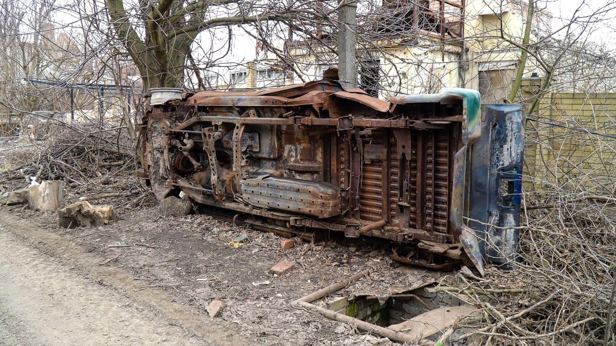 Tuhoutunut ajoneuvo kyljellään tien vieressä.