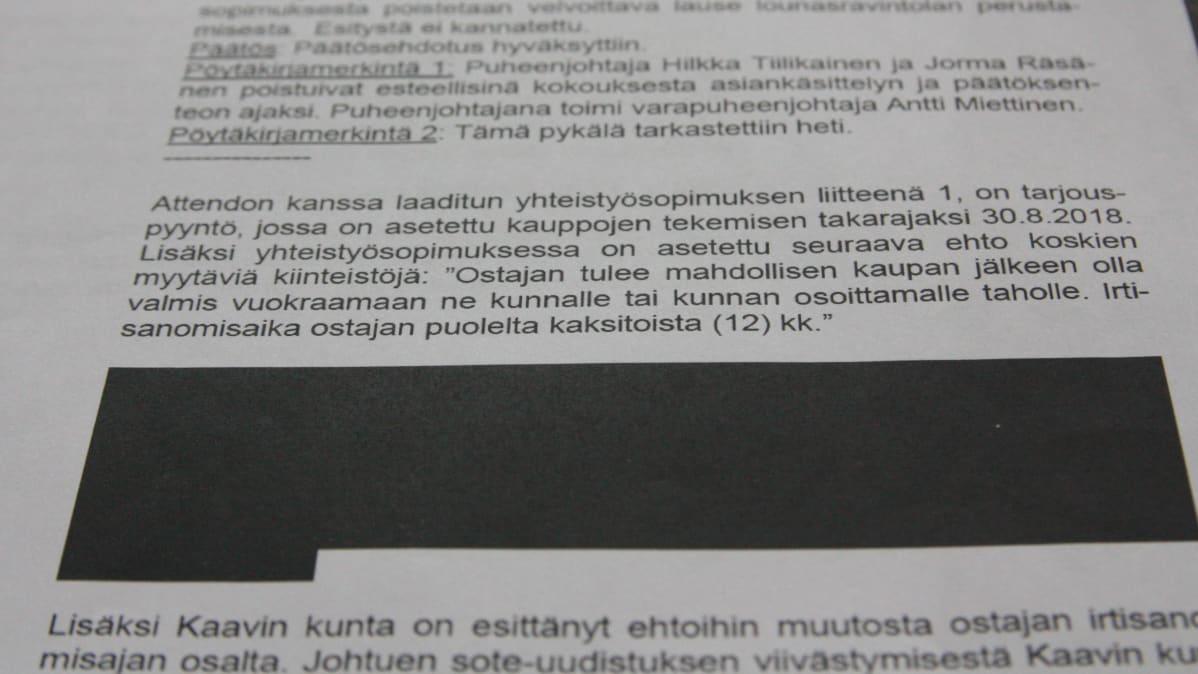 Valokuva pöytäkirjasta, jonka tekstistä osa on salattu.