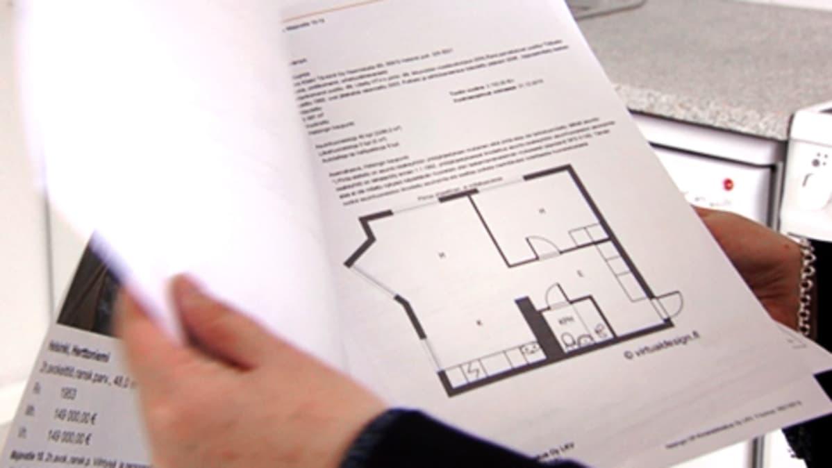 Asunnonostaja selaa papereita asuntoesittelyssä.