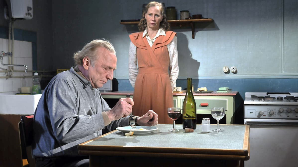 Näyttelijä André Wilms aterioi pöydän ääressä Kati Outisen katsellessa taustalla.