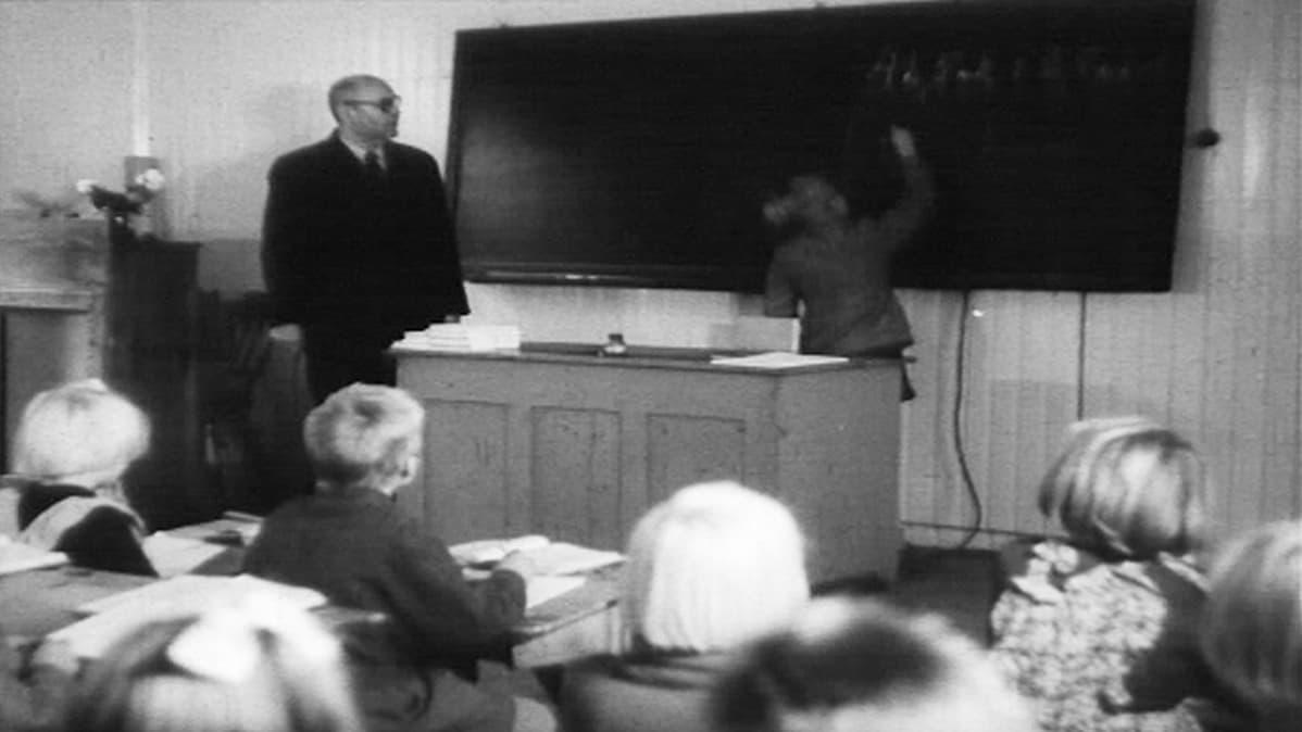Oppilas kirjoittaa luokan edessä taululle, opettaja seuraa vierestä.
