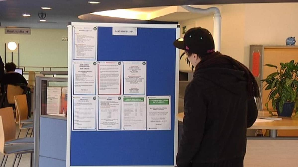 Nuori tutkii ilmoitustaulua TE-keskuksessa.