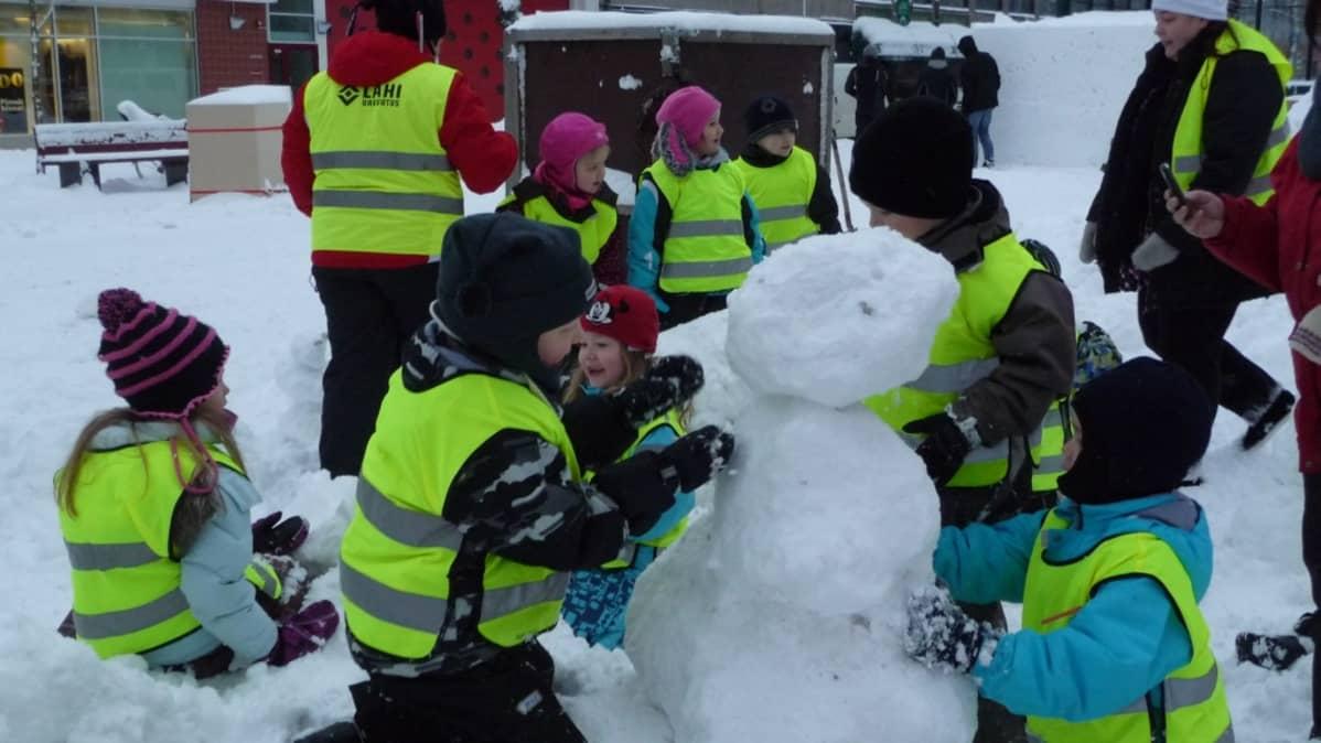 Lapset tekevät lumiukkoja.
