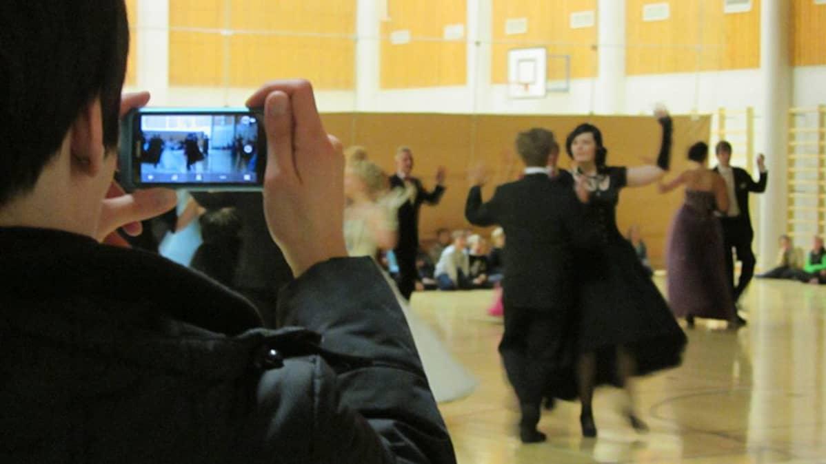 Nainen kuvaa kännykällä kilpatanssijoita