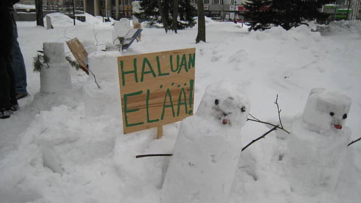 Lumiukkoja Ilmastolain Puolesta -tempauksessa Joensuun keskustan puistossa.