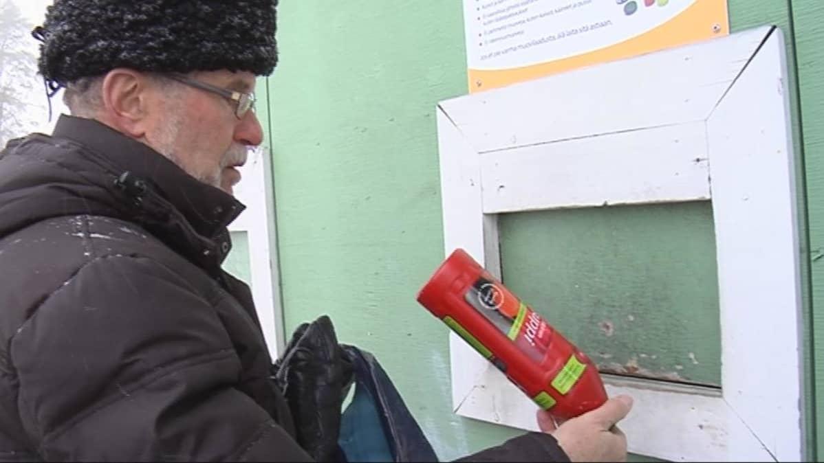 Mies palauttaa ketsuppipulloa muovijätteisiin.