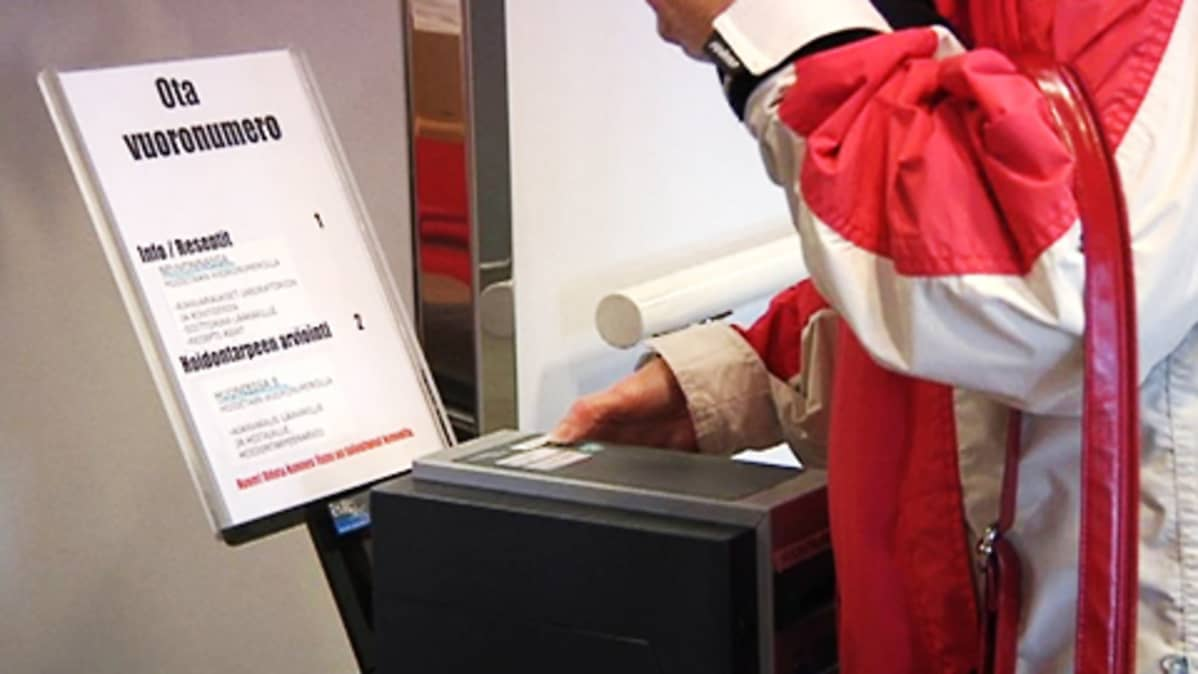 Asiakas ottaa laitteesta vuoronumeroa terveyskeskuksen aulassa.