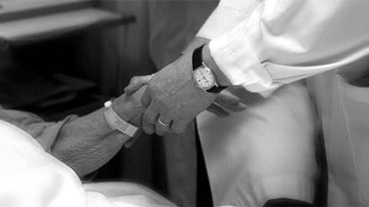 Lääkäri pitää potilasta kädestä.