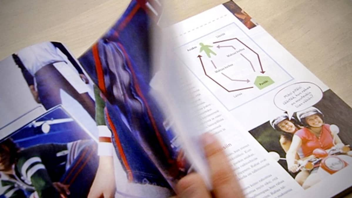 Oppilas selaa yhdeksännen luokan yhteiskuntaopin kirjaa.