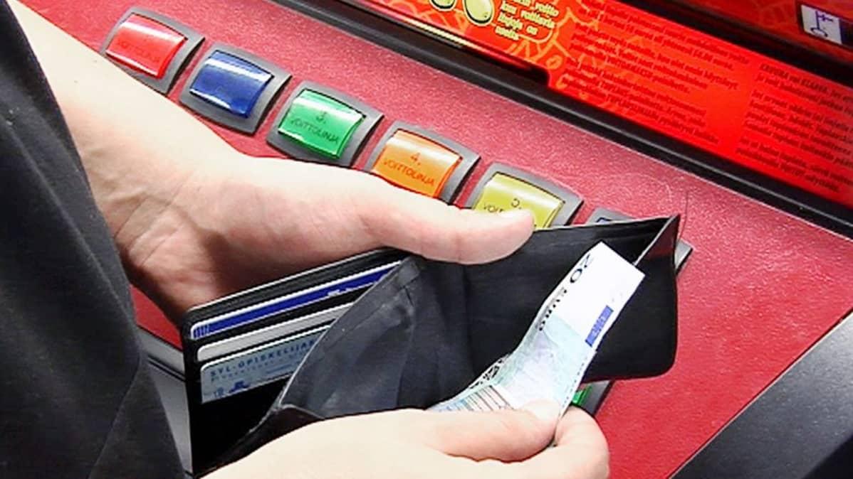 Nuori laskee rahojaan peliautomaatin äärellä.