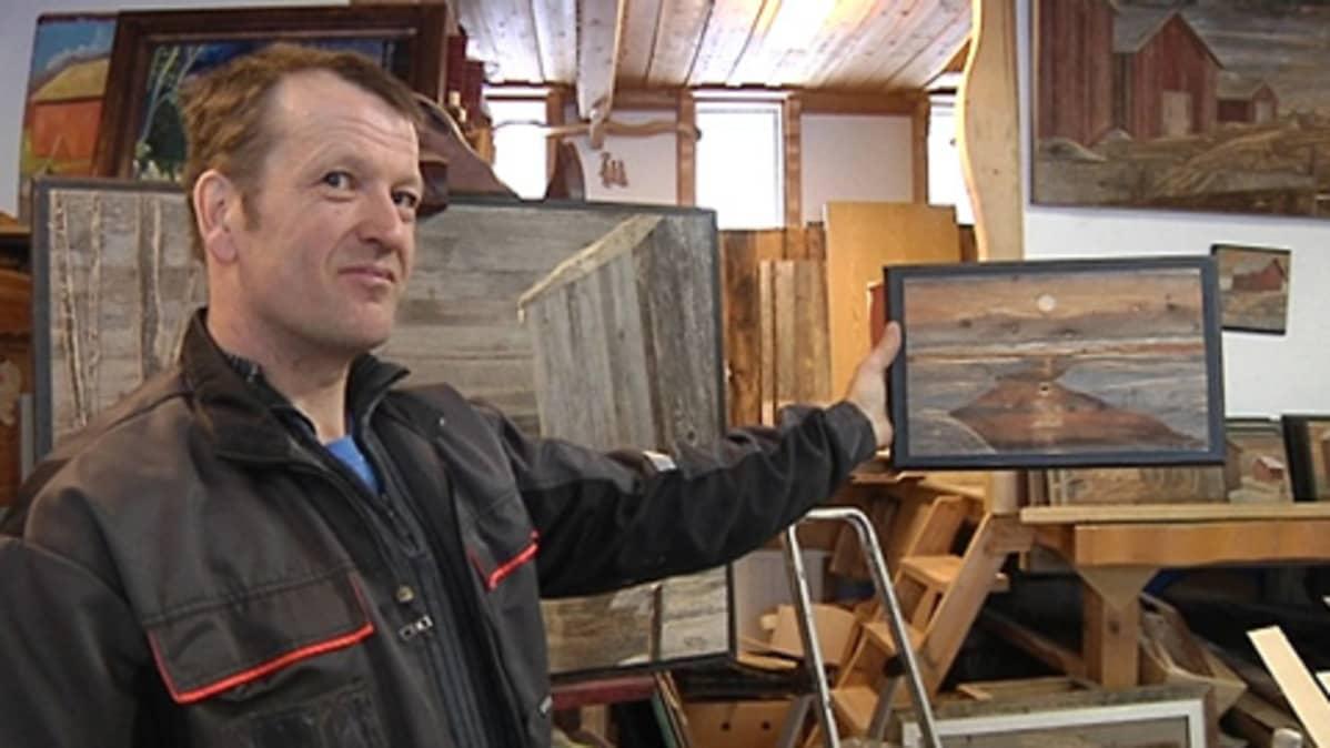 Kuvassa taitelija Sixsten Ahlsved esittelee taidettaan.