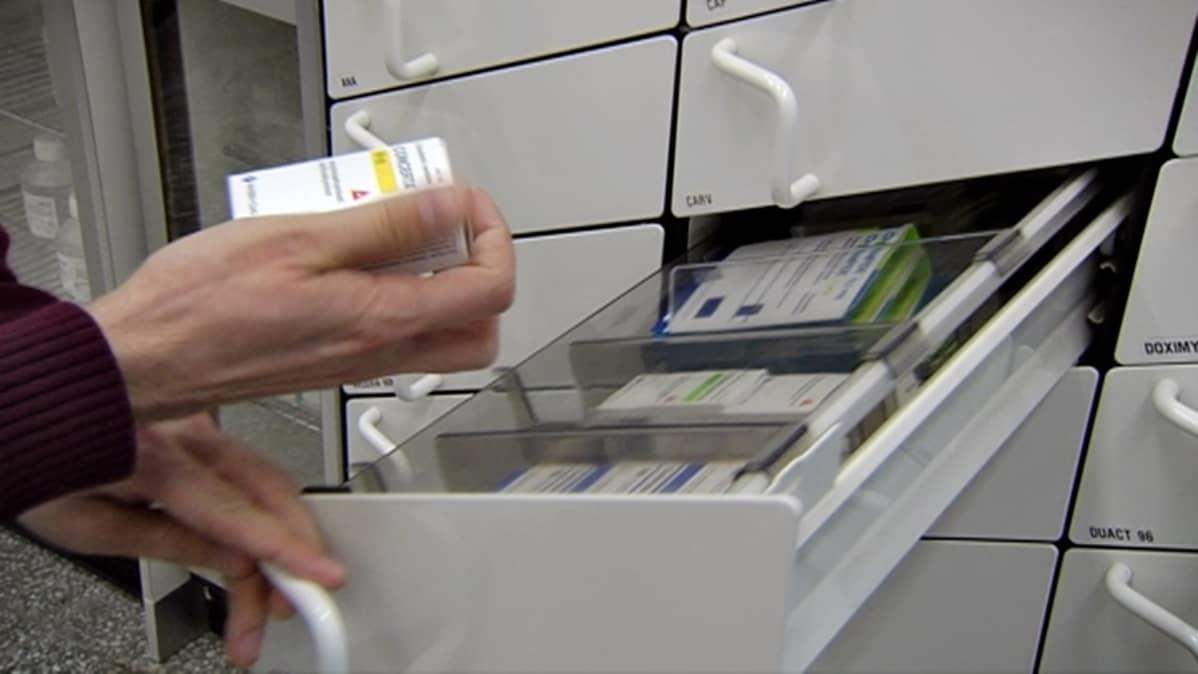 Apteekkari ottaa lääkkeitä vetokaapista.