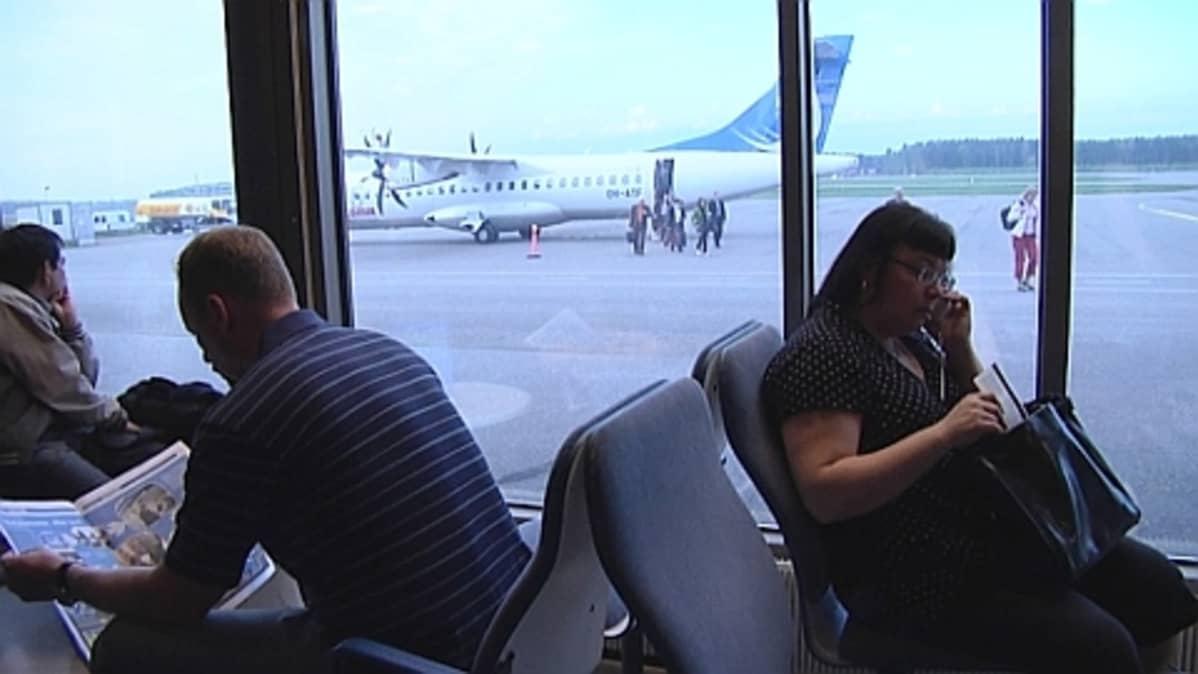Matkustajia odottamassa lentoa Porin lentokentällä.