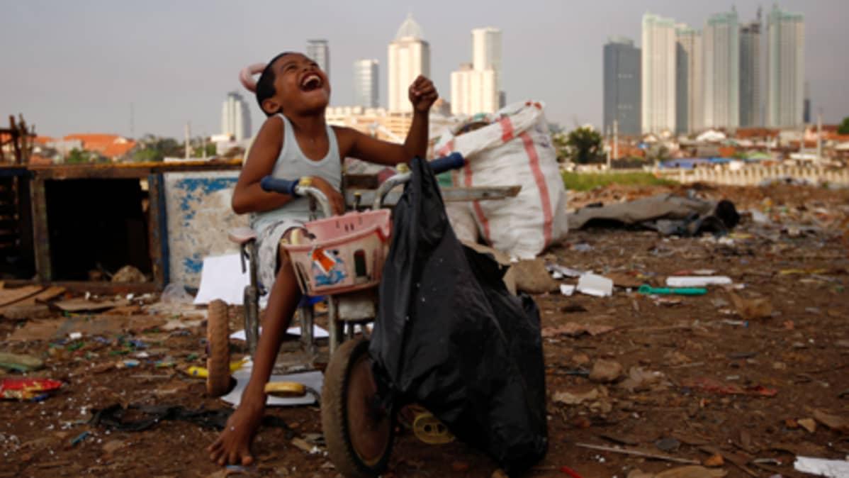 Indonesialainen poika leikkii Jakartan slummissa