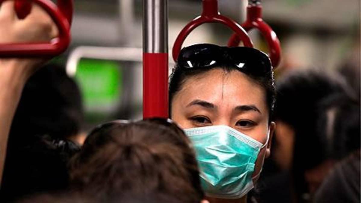 Nainen Hong Kongin metrossa hengityssuojain kasvoillaan.