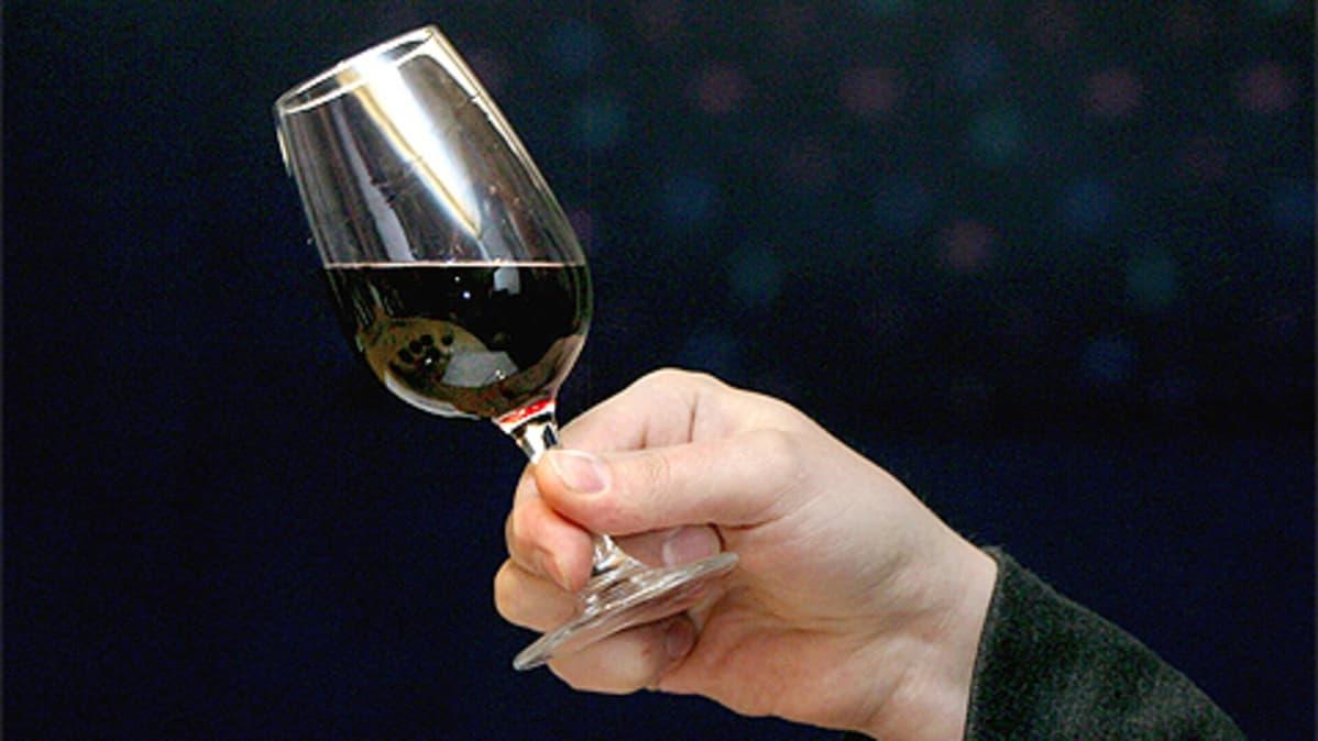 Mies pitelee viinilasia