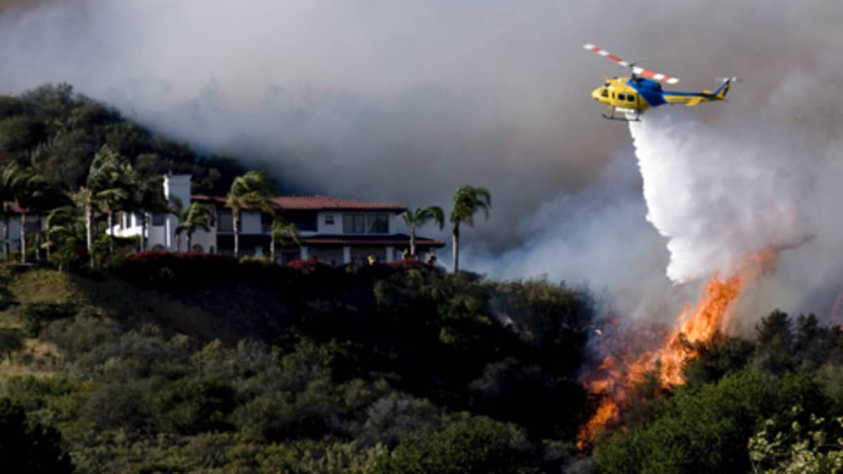 Helikopteri laskee sammutusvettä liekkeihin metsäpalojen vaivaamassa Santa Barbarassa Kaliforniassa.