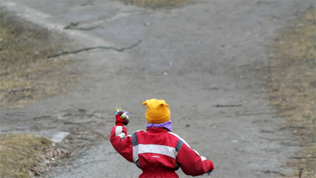 Pieni lapsi seisoo ulkona teiden risteyksessä.
