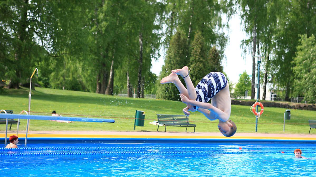 Poika hyppää ulkoaltaaseen