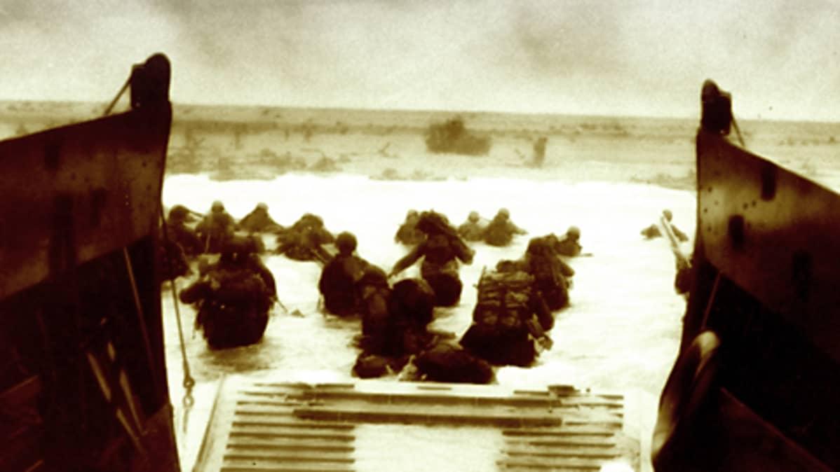 Sotilaat kahlaavat vedessä Normandian rannikolla. Maihinnousualuksen porttiaukko.