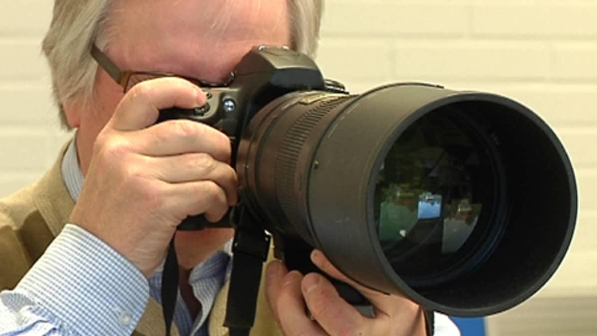 Mies kuvaa kameralla, jossa on iso objektiivi.