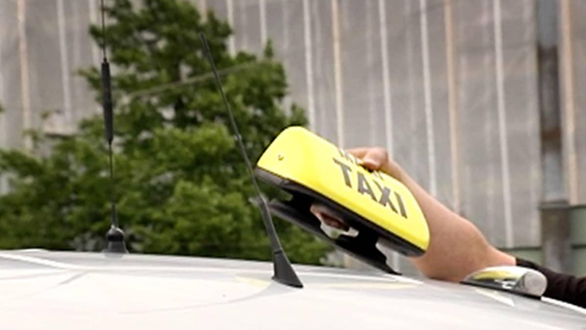 Mies ottaa taksikupua muistuttavaa tunnusta pois auton katolta.