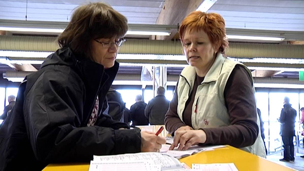 Virallinen valvoja Kirsi Lindqvist opastaa Sirkka Haverista pelikupongin täyttämisessä.