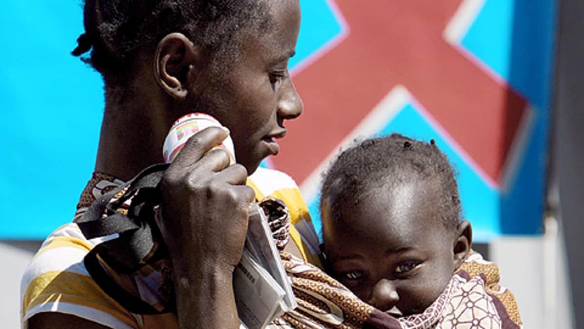 Etelä-Afrikkalainen äiti, sylissään vauva kantoliinassa. Taustalla HIV-nauha.