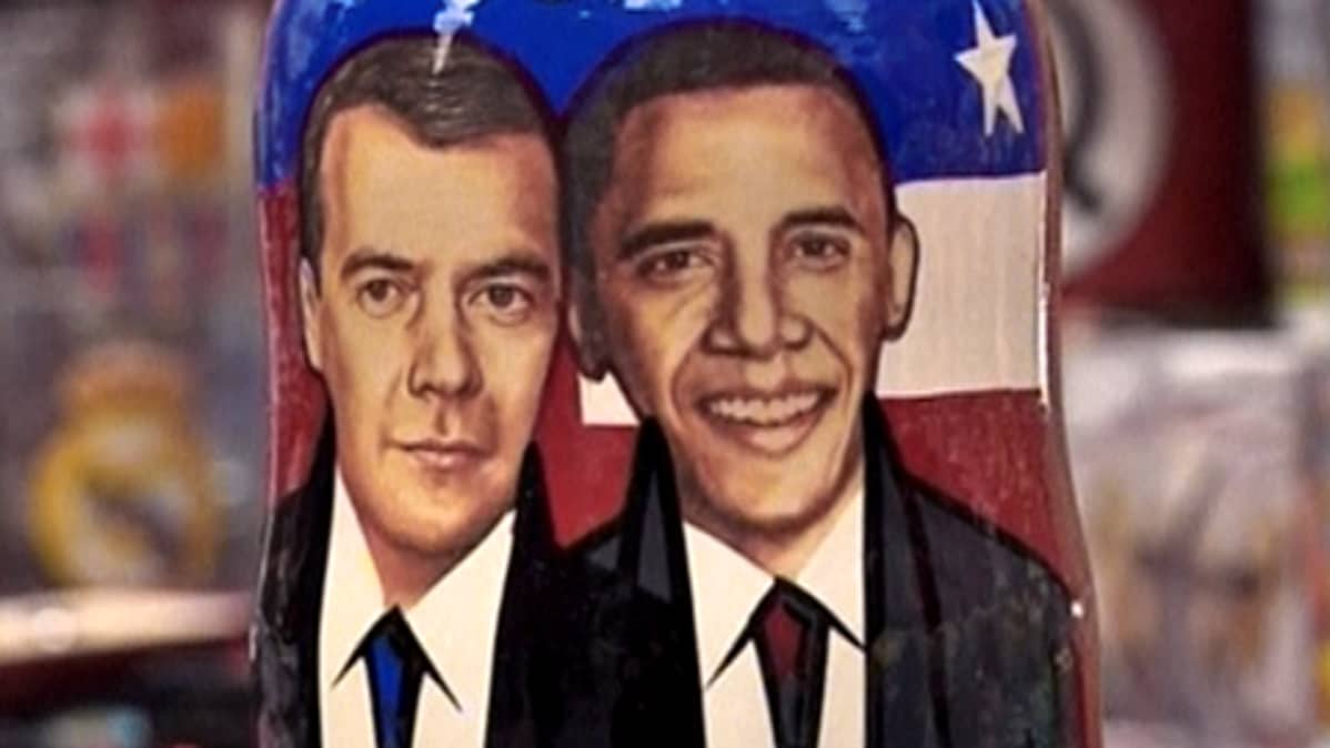 Dmitri Medvedevin ja Barack Obaman maalatut muotokuvat Yhdysvaltain lippu taustanaan.