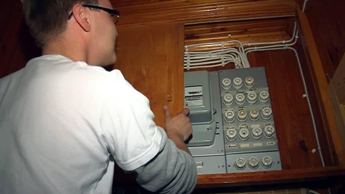 Mies tarkastaa sähkömittaria.