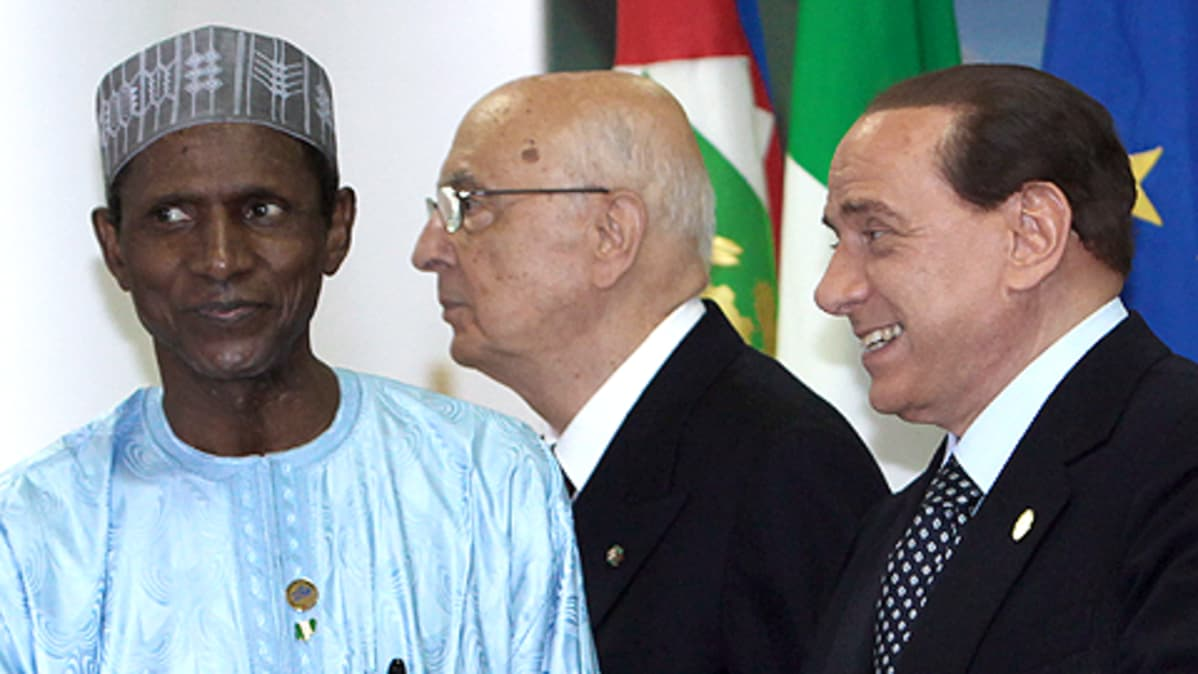 Nigerian presidentti Umaru YarAdua (vas.) ja Italian pääministeri Silvio Berlusconi (oik.) G8-huippukokouksessa 2009. (Taustalla tuntematon).