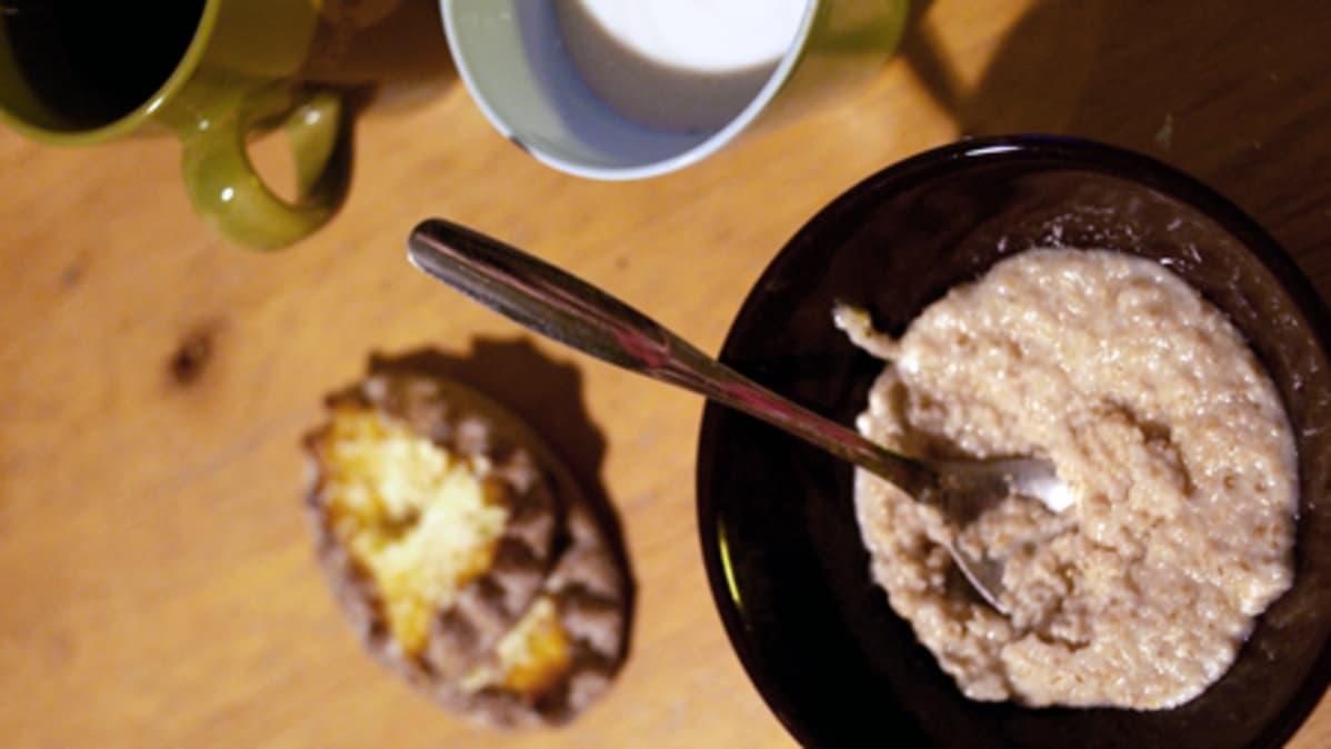Aamiaispöytä: riisipiirakka, kahvikuppi ja puurolautanen.