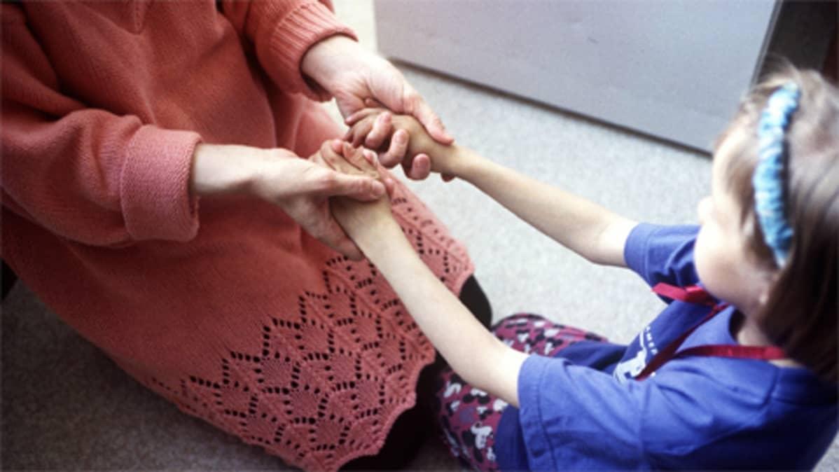 Äiti ja lapsi istuvat lattialla pitäen toisiaan käsistä