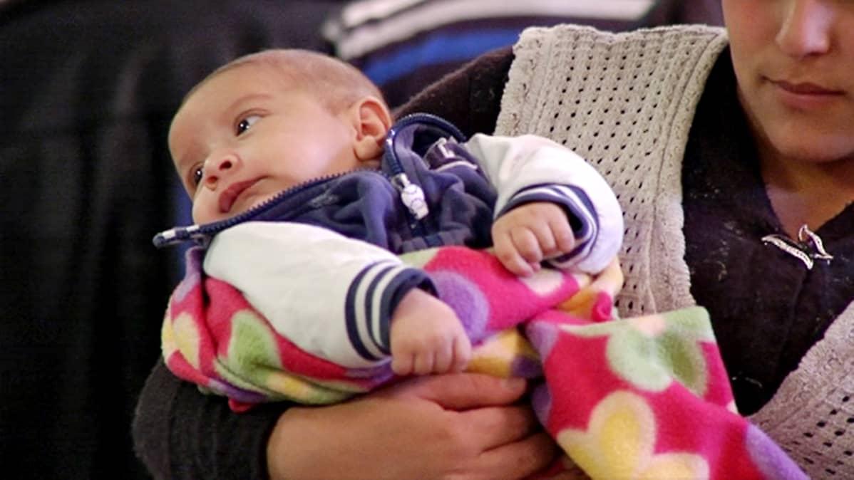 Nuori äiti pitää pientä lasta sylissään.