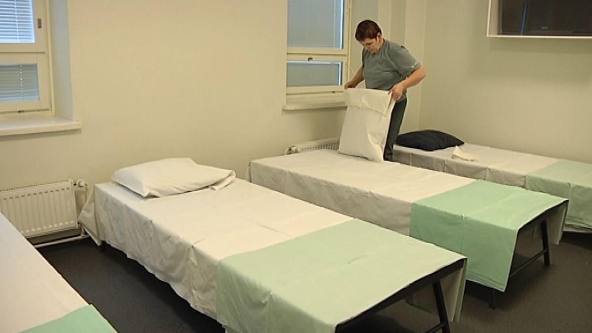 Sänkyjä pedataan uusia yöpyjiä varten Hietaniemenkadun palvelukeskuksessa.