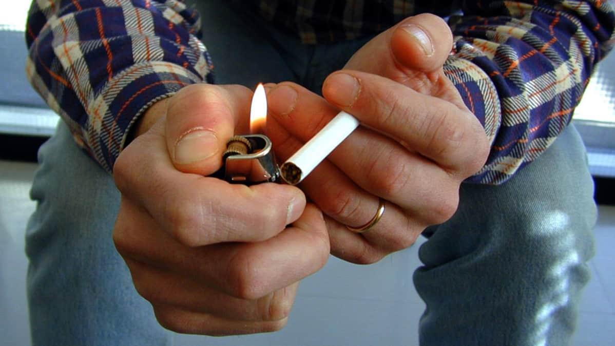 Miehen käsissä sytkäri ja tupakka.