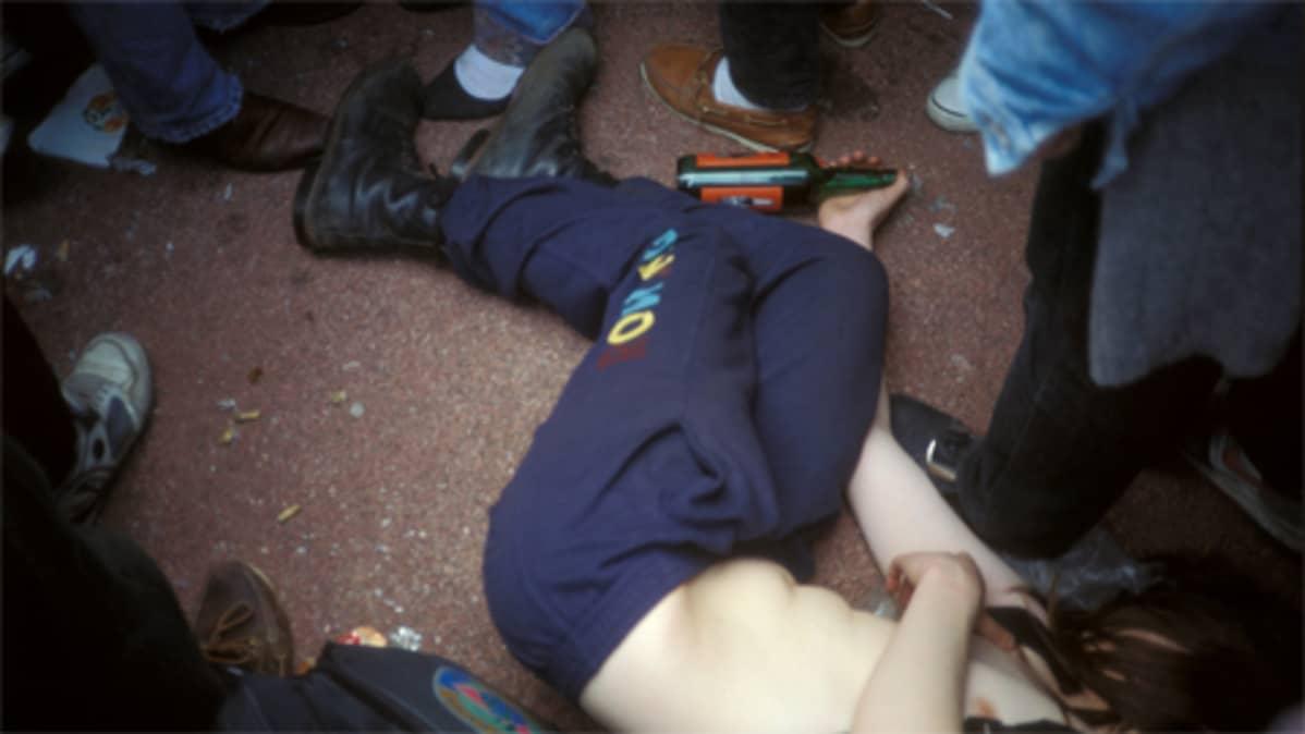 Juopunut nuori makaa maassa pullo kädessään.
