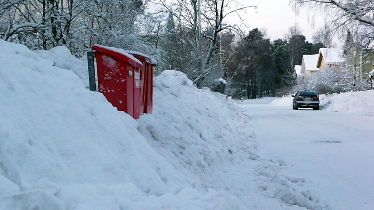 Postilaatikot törröttävät lumikasan keskellä.