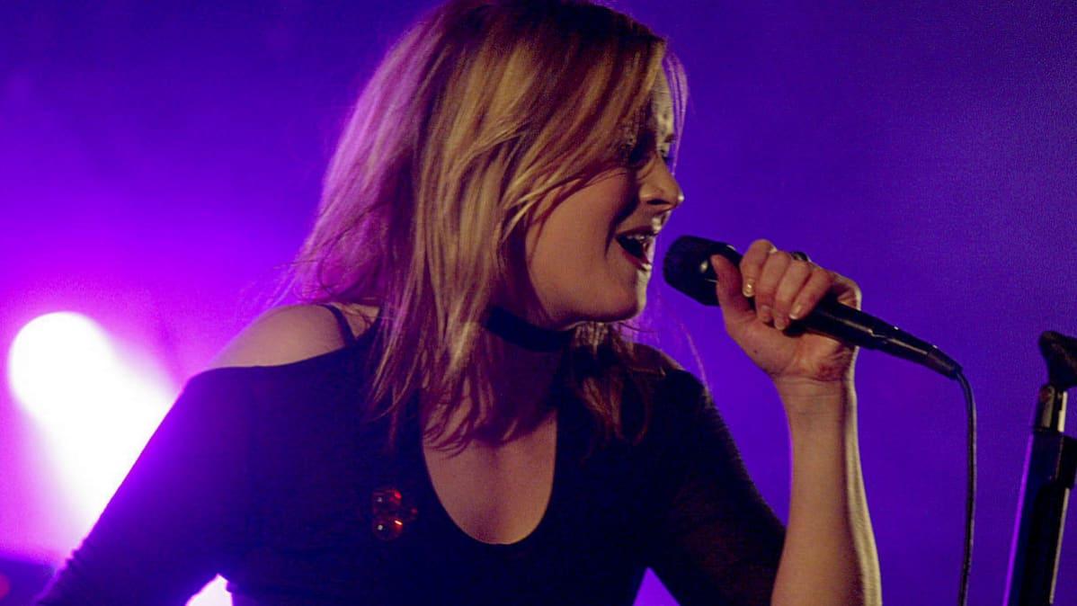 Jonna Tervomaa lavalla mikrofoni kädessä