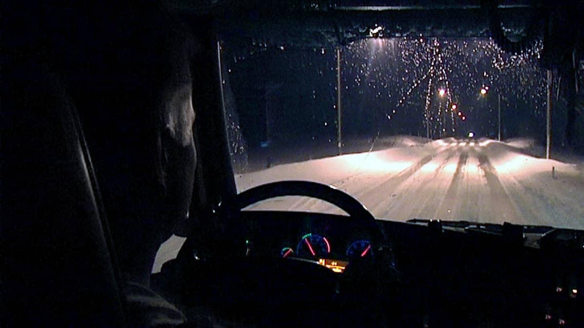 Rekkakuski ajaa rekkaa öisellä tiellä.